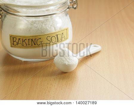 spoonful of baking soda and a jar on the wooden background