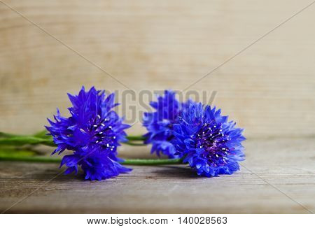 Bouquet of cornflowers on an old wooden surface