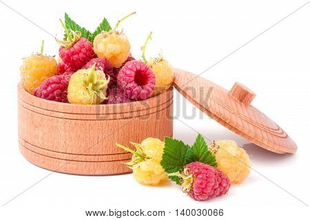 red and yellow raspberries in a wooden bowl isolated on white background.