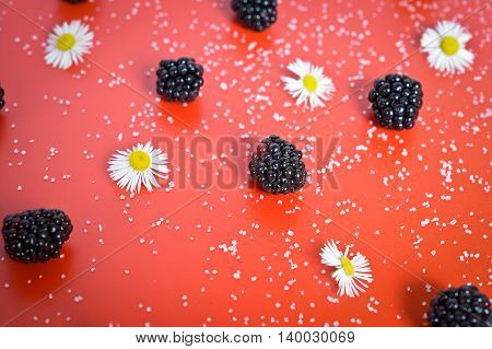 blackberries and red sugar on the table background and texture