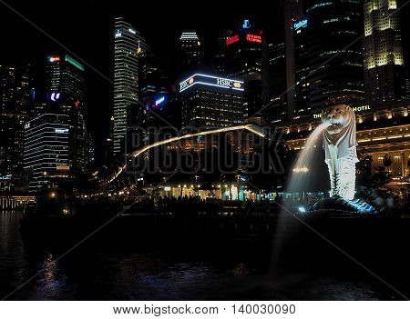 Night charm of Singapore.  Singapore, Asia - June 05, 2016 Merlion- statue, a national symbol of Singapore squirting water at Merlion Park in the evening scenery