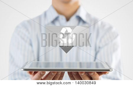 Businessman holding in hand tablet with recycle icon