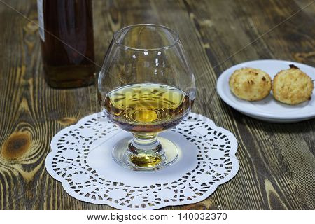 A glass of brandy with cookies on wooden background close up