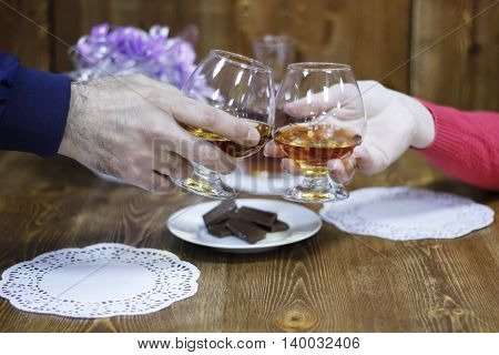 Romantic date night. Holding glasses of brandy say a toast
