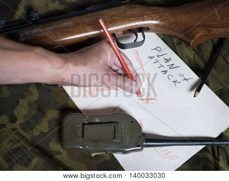 Male hand with pencil planning an abstract attack on a piece of paper a gun and radio laid on a camouflage uniform. Closeup studio shot