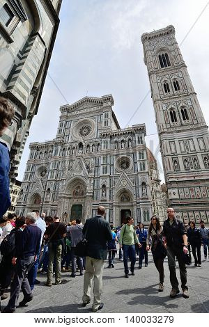 FLORENCE, ITALY - APRIL 27: Tourists on Piazza del Duomo in front of the cathedral of Florence - Dom Santa Maria del Fiore, bell tower Campanile di Giotto and Baptistery on April 27, 2013 in Florence