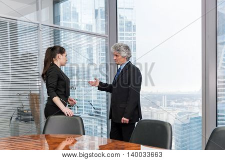 Boss instructs young secretary in modern office
