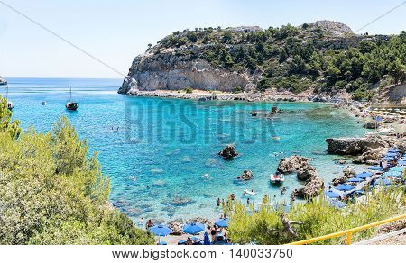 Rhodes, Greece- June 21 2016. Tourists enjoying the sea during a warm summer day in the popular Antony Quinn bay or Rhodes island. Named after the famous actor who bought the land during the filming of The Guns of Navarone in Rhodes. However, it was later