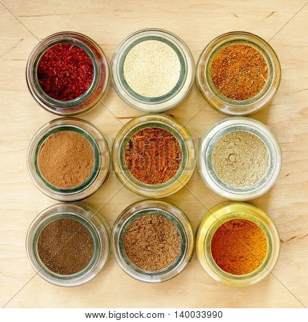 many different spices in glass jars and a special seasoning for pilaf in the middle of a top view / aromatic seasoning for cooking in the kitchen