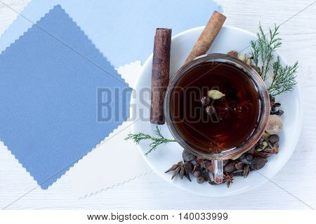 tea with spices in a transparent mug on a background of cards for inscriptions top view / festive flavored tea