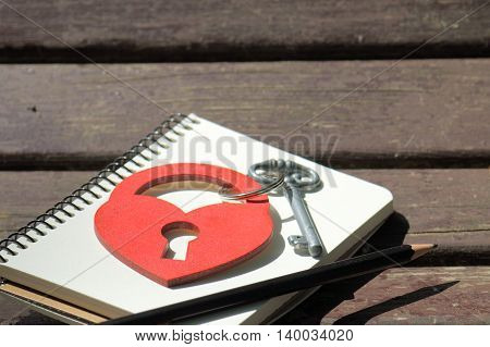 heart symbol in the form of a padlock with key on a background of a notebook with a pencil on a wooden background / love notes