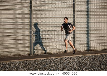 Full length portrait of athletic man running along beautiful grey wall outdoors, muscular build young runner working out while jogging in the park. Sunset