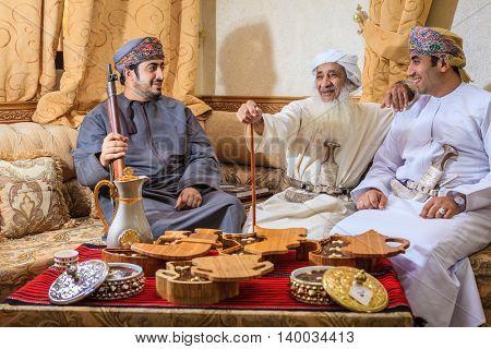 NIZWA, OMAN, MAY 27, 2016: Family of Omani halwa makers behind a table with freshly made halwa