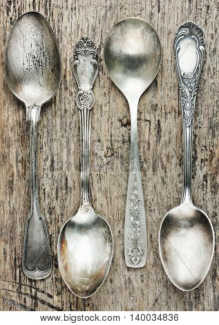 Vintage spoons collection on old wooden background top view