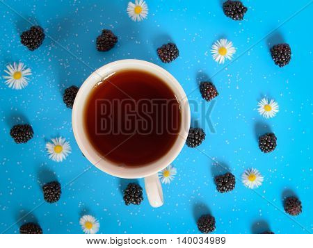 tea cup on blue table with flower and blackberries