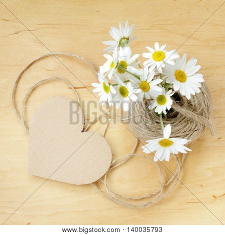 bouquet of daisies on a wooden table and a simple heart symbol top view / retro romantic story