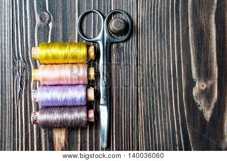 Accessories for sewing on dark wooden table - thread, scissors. Copy space.