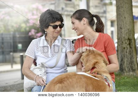 Blind woman and home carer relaxing on bench