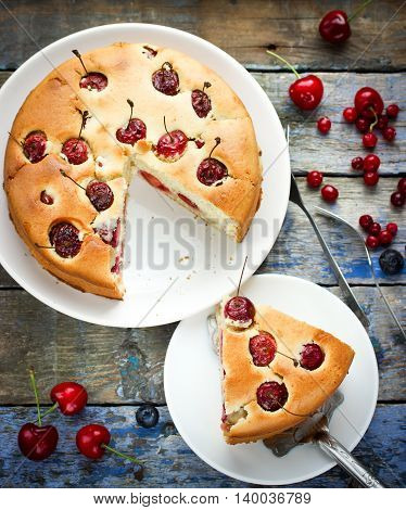 Sponge cake with cherries on old wooden background in a rustic style top view