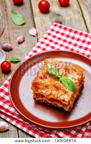 Meat lasagna on a dark wood background.