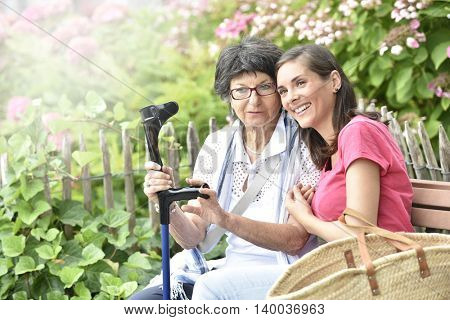 Senior woman with home carer sitting in park