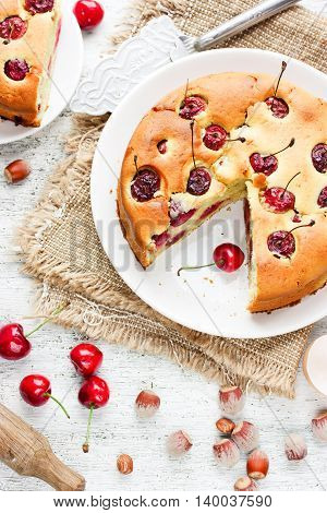 Cherry pie - delicious cake with cherry and nuts on white kitchen table with ingredients top view