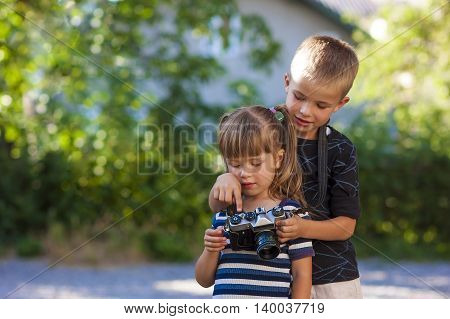 Little boy and girl learning how to use photo camera