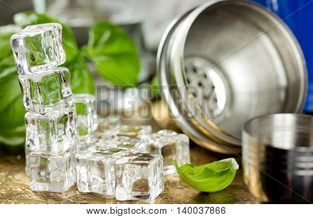 Ice cubes fresh basil shaker to prepare refreshing drink in bar selective focus