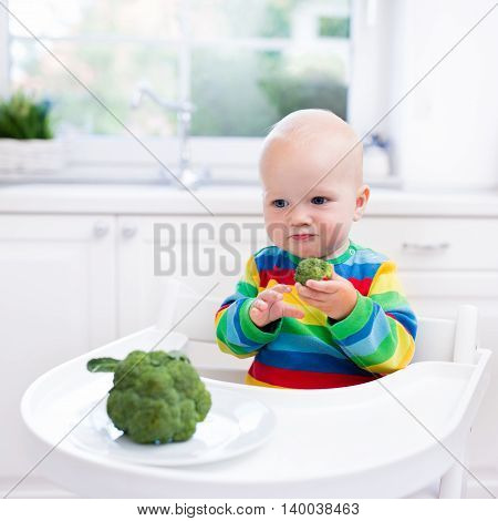 Little Boy Eating Broccoli In White Kitchen