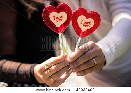 man and woman holding candy in the shape of a heart