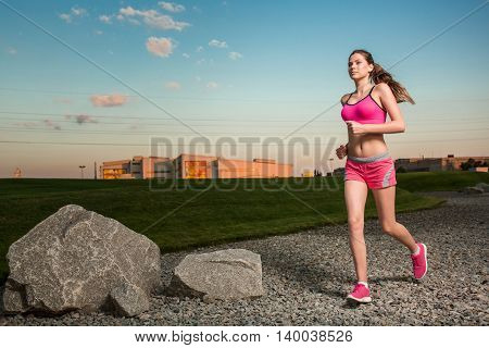 Running woman. Runner jogging in sunny nature. Female fitness model training outside in sunset sky background.