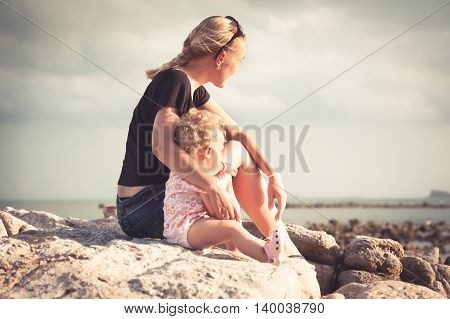 mother and her baby sitting together on the beach coast during sunset and looking into the distance. Mother embrace child and the sunlight illuminates their faces. Mother and child sitting in profile