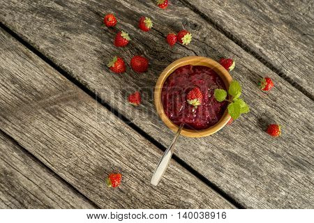Top down view on jam in bowl with fruit over long plank on table with weathered surface.