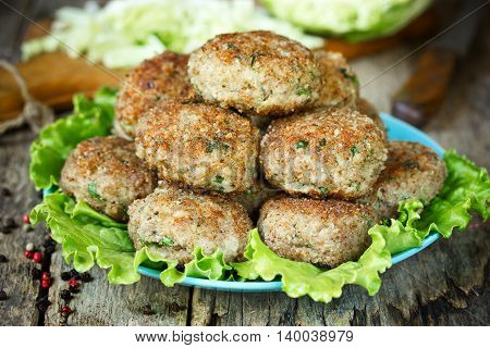 Cutlets of pork with cabbage and green herbs. Meatballs with vegetables on a plate with lettuce. Rural food recipe selective focus