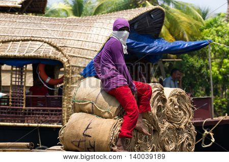Allepey, Kerala, India, March 31, 2015: Some men transport overload empty bags by boats