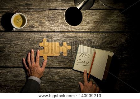 Conceptual image with inspirational message You Can of a man working on a puzzle on a rustic wooden table by the light of a lamp with coffee and a notebook with the handwritten words overhead view.