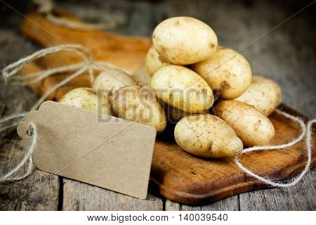 Young potatoes on a wooden board with a paper tag for text. Product rich in carbohydrates selective focus