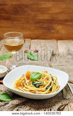 pumpkin spinach pecan pasta on wooden background