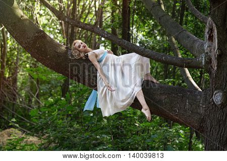 Young beautiful girl dressed in a tunic lying on a big tree in a park