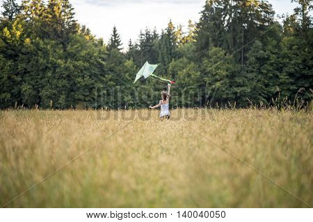Rear view on a single person running through prairie with kite and large evergreen forest in background with copy space.