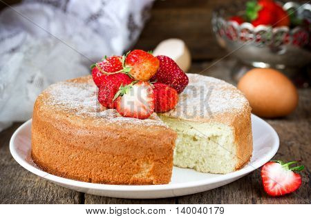 Victoria sponge cake with strawberry on old wooden background. Biscuit with summer fruit in a rustic style selective focus