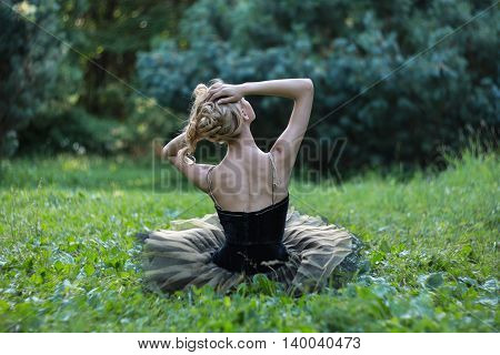 Beautiful girl sitting and resting on a grass in a summer park
