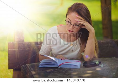 Girl with book reading at the park