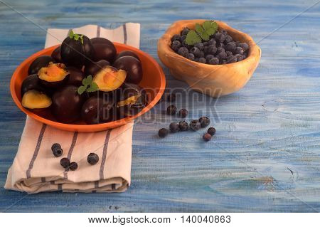 An orange plate full with plum and wooden bowl full with blueberry on blue wooden table