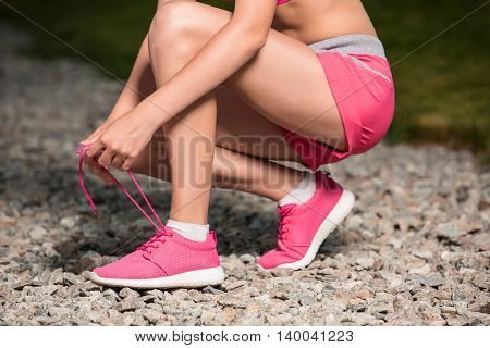 Running shoes - woman tying shoe laces. Closeup of female sport fitness runner getting ready for jogging outdoors on park path in late summer or fall.