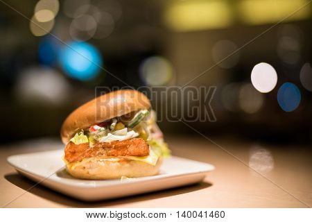 Fried fish burger with vegetable and cheese under spotlight blur bokeh dark background