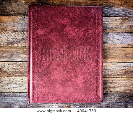 the book is red on the old wooden boards close up top view. tinted photo retro toned image