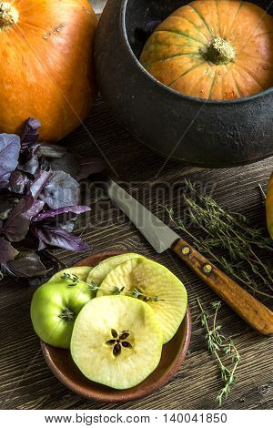 Pumpkin, a kitchen knife, Basil, thyme, green apples