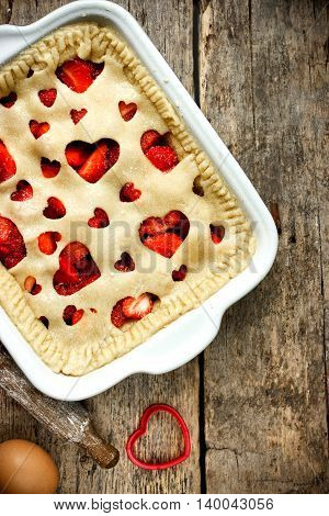 Preparation delicious homemade cake with fresh strawberry. Raw pie of shortcrust dough decorated with hearts on a wooden table. Summer food background kitchen concept top view blank space for text