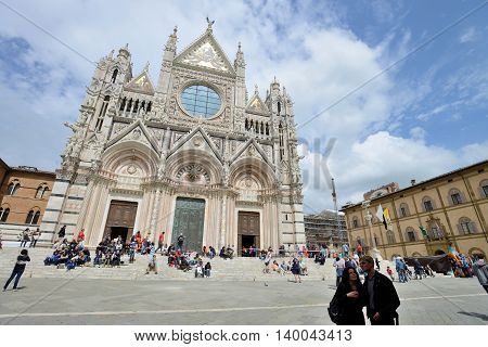 SIENA, ITALY - APRIL 28: Tourists in front of cathedral of Siena, Italy, April 28, 2013. Designed, completed between 1215 -1263 on the site of an earlier structure, a major tourism attraction in Siena